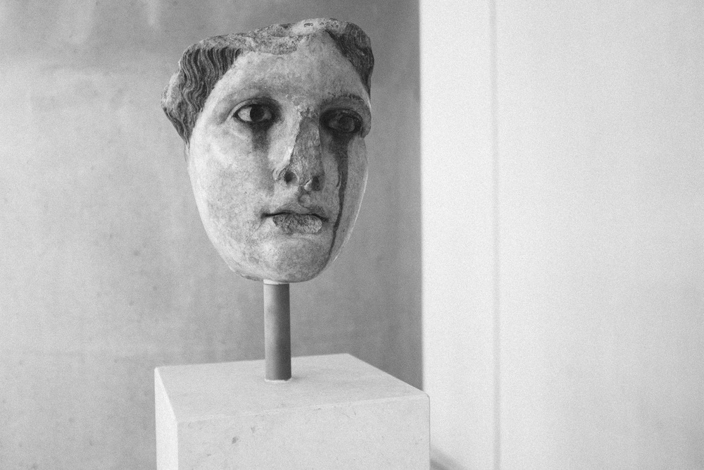 Photo 75. Marble head with a streak on its face.  Likely a product of weather meeting formerly inset materials used for the eye.  National Archaeological Museum, Greece, 2014.