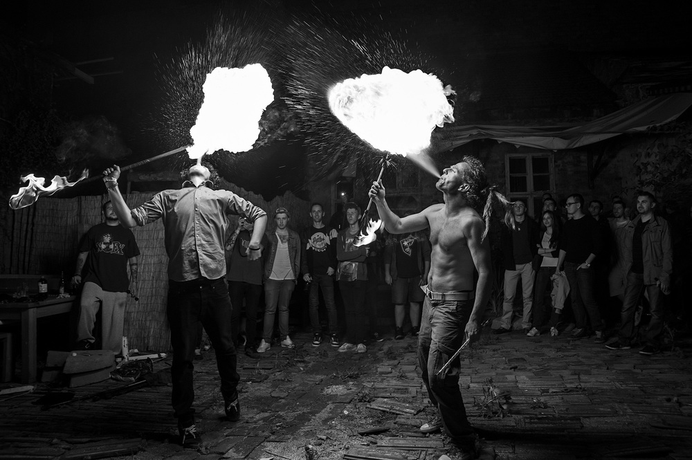 Kiss Balazs, right, a Hungarian 'fire breather' from Oradea, Romania performs along with members of his juggle shop in front of a crowd of onlookers at a nightclub in Oradea, Romania on May 17, 2013.