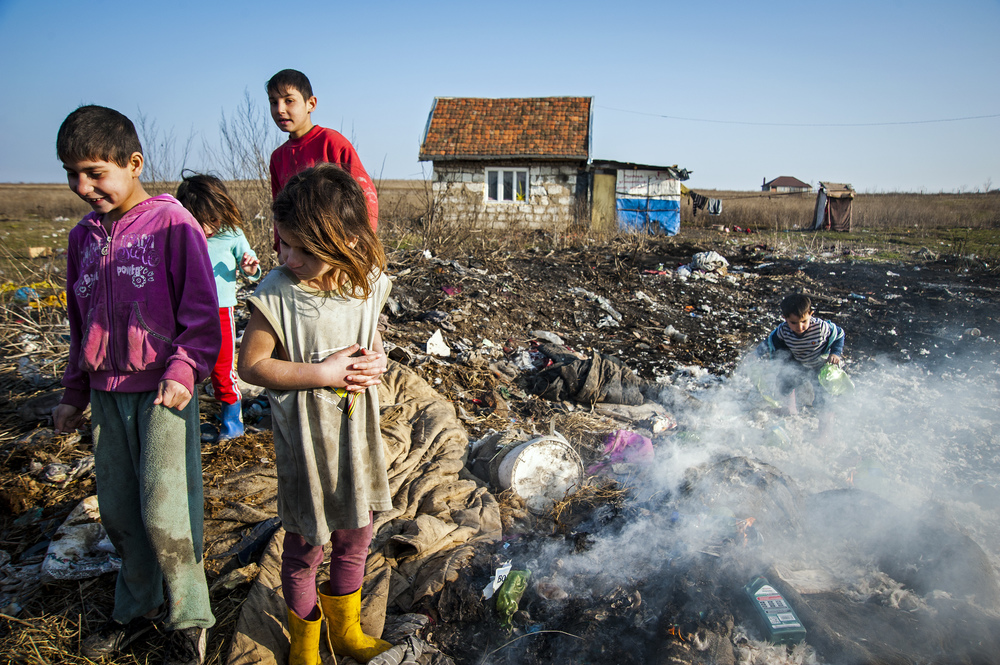 Eight-year-old Andrea Hendre, right, shivers from the February cold as she and her three cousins burn blankets and clothing in a rubbish pile outside their home on February 19, 2013. The clothes and blankets had been soiled by the younger children during the night and, without running water, there is no way to clean the them.