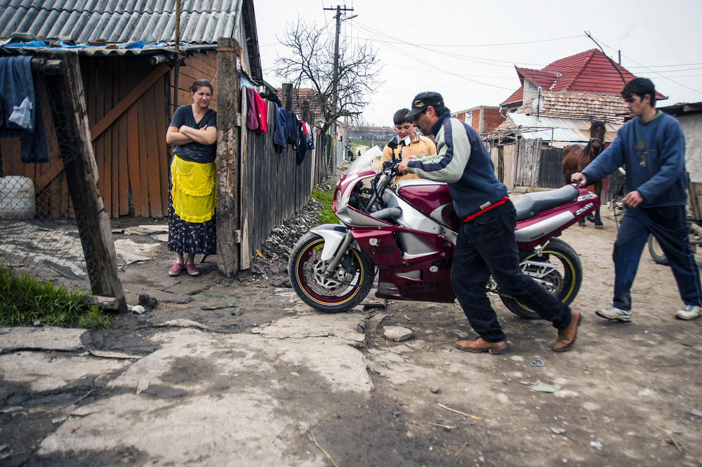 Stefan Demian pushes a motorcycle into his front yard in Cheriu, Romani on March 20, 2013. Though many of the Romani struggle to survive, others live more comfortably, bardering, trading, buying and selling in nearby villages.