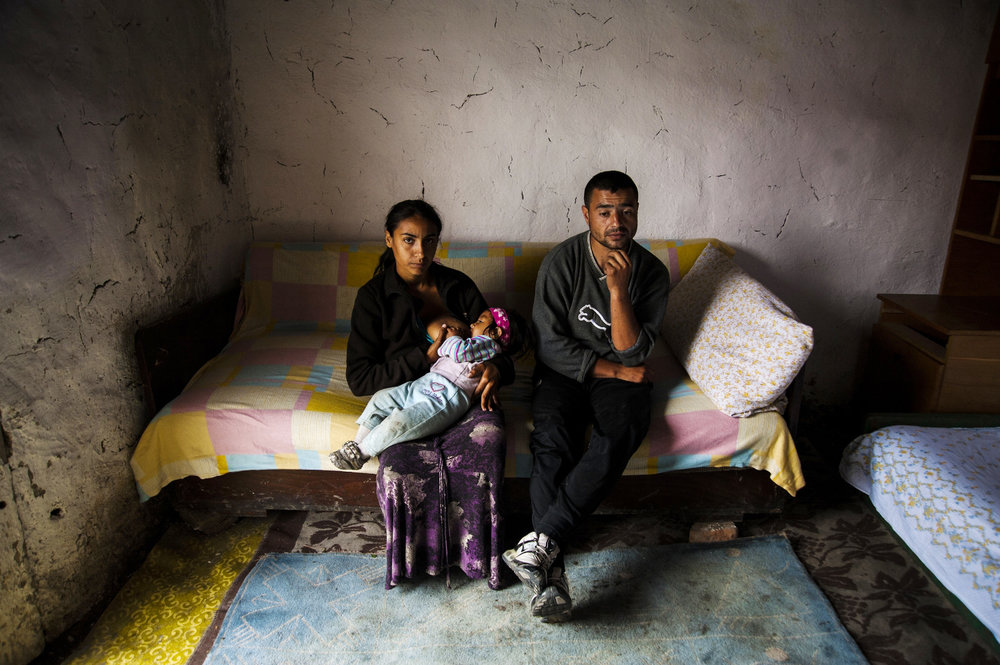 Radu Hendre sits with his breastfeeding wife, Cosmina, and their unnamed child in their one-room hut in the small gypsy colony of Cheriu, Romania on May 14, 2013. Hendre is unable to travel to the nearby city of Oradea to find work because local gypsy money lenders have vowed to kill him unless he repays his debts of nearly $1,000 (US) that he borrowed to buy mud hut.
