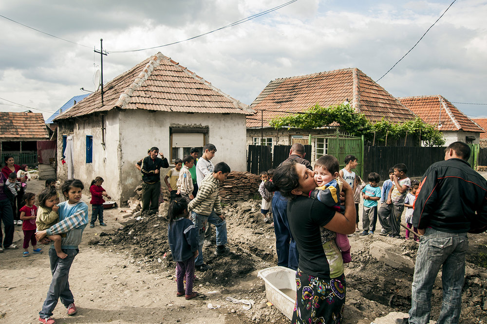 Romani residents of Cheriu, Romania fill the streets as one family gets running water installed into their home on May 14, 2013.