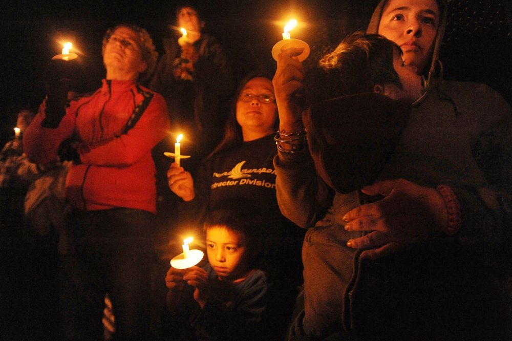 Dozens of neighbors and residents from the community surrounding Saturday's shooting in Colorado Springs, Colo.attend an evening candlelight vigil overlooking the East Platte Avenue scene on Sunday, November 1, 2015.