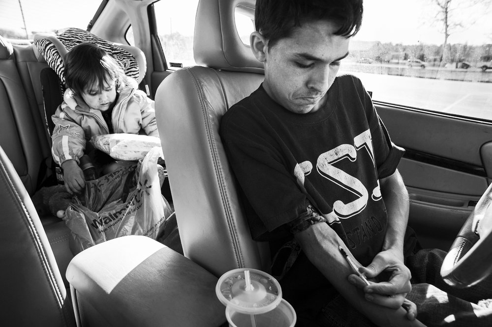 A nineteen-year-old from shoots up black tar heroin while his two-year-old daughter plays in the backseat of the family car parked just outside a local grocery store in Jackson, Ohio on November 13, 2013. The self-professing addict uses heroin to help combat the pain of his severe Scoliosis and Neurofibromatosis.