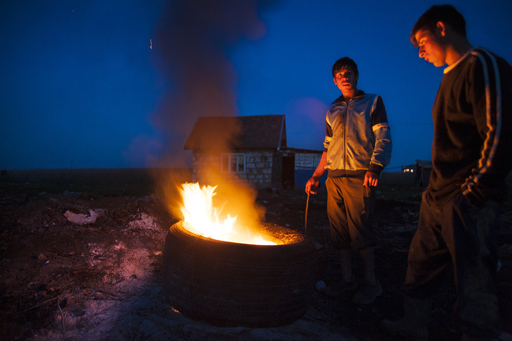 Dobrin Hendre, center, and his older brother, Florin, stand guard while they burn the tires that their father brought home from the city to be burned for their steel belts on April 17, 2013.