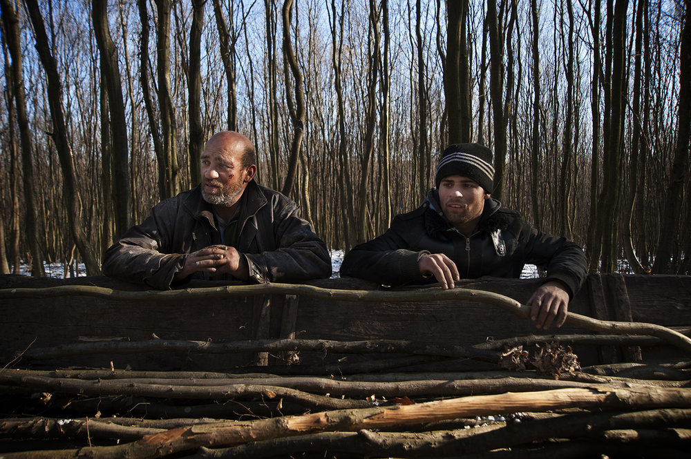 Florin Hendre, right, and his uncle, Florin Lacatus, fill their carriage with wood to heat their homes in the nearby village of Cheriu.