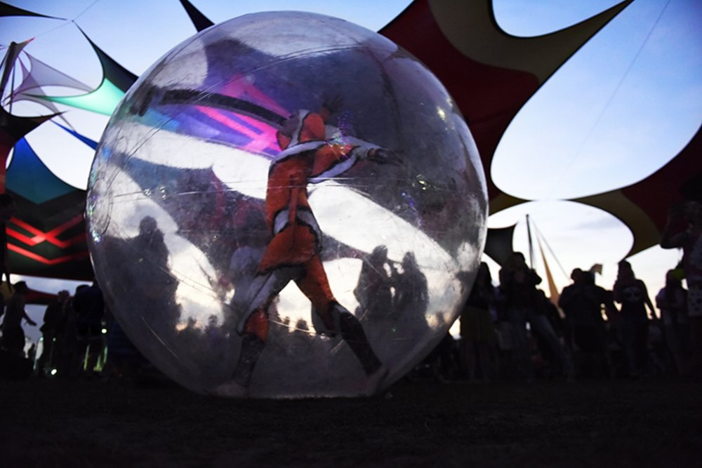 A dancer makes her way through the festival grounds in an inflated plastic ball during the second day of the Okeechobee Music Festival in Okeechobee, Fla., on Saturday, March 5, 2016.