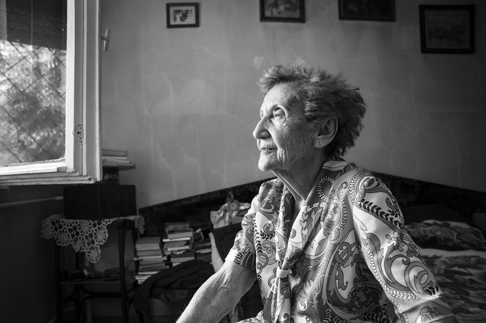 "Gabriella (Hamlet) Bóné, a survivor of Auschwitz Birkenau, sits on her bed and looks out the window of her small ground-level apartment in Oradea, Romania on August 23, 2013. Bóné vividly remembers the deportations when she was just fifteen years old. ""The Hungarian police crammed us into wooden train cars that had barbed wire covering the small windows. We traveled without food and with very little water for nearly a week without knowing what fate lay before us. We arrived at Auschwitz having barely slept only to be inspected by Dr. Mengele himself and the other SS officers."""