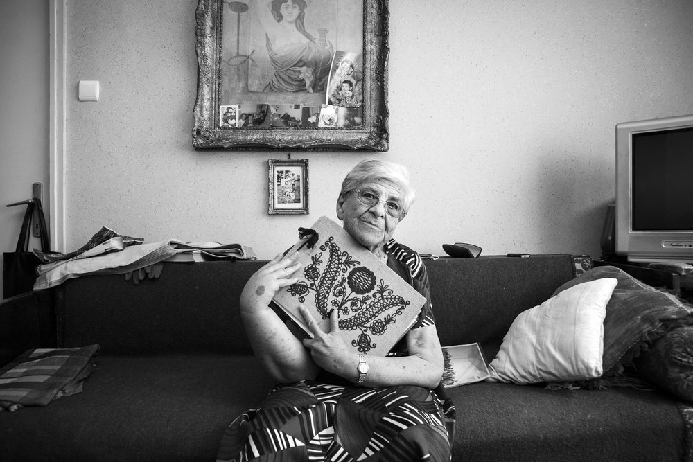 "Auschwitz survivor, Iudit Varadi, 87, poses for a portrait with her family photo album at her home in Oradea, Romania on August 18, 2013. ""My brother and mother died in the camps. Altogether, I lost around eighty members of my extended family in the Holocaust, so when I returned home I was alone. I had to start my life all over.""  *Mrs. Iudit Varadi has since passed away following the publication of the story."