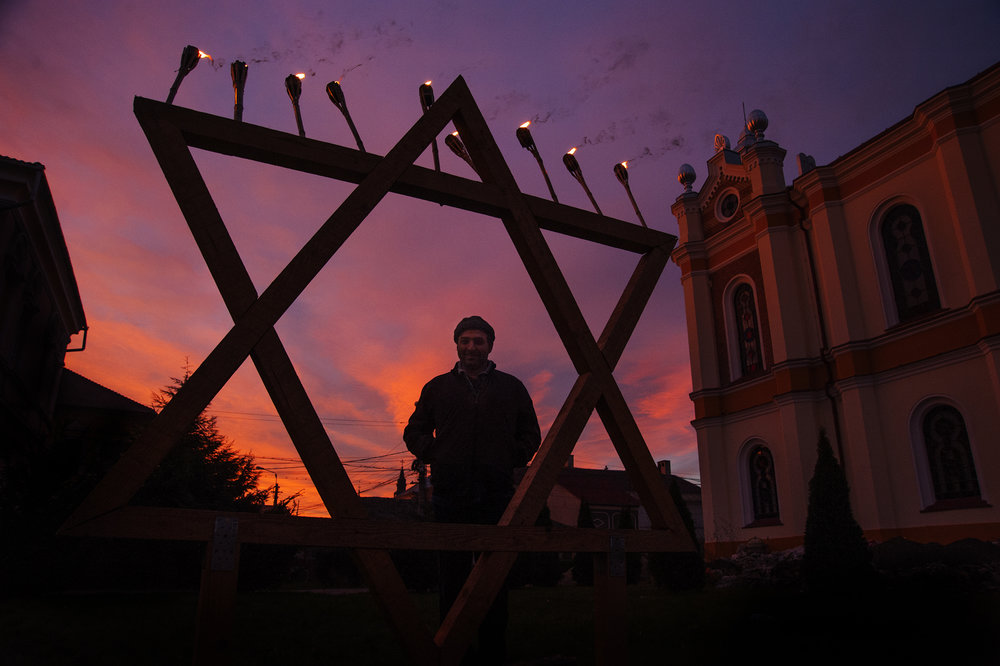 The sun sets over the Great Synagogue on the final day of Hanukkah on December 23, 2014. Tomer Corinaldi, center, visits from Israel to celebrate Hanukkah with the Jewish community and teach lessons from the Torah, while the long-term acting Rabbi from Tel Aviv, Shraia Kav,  not pictured, returns to Israel for a week to visit with family.