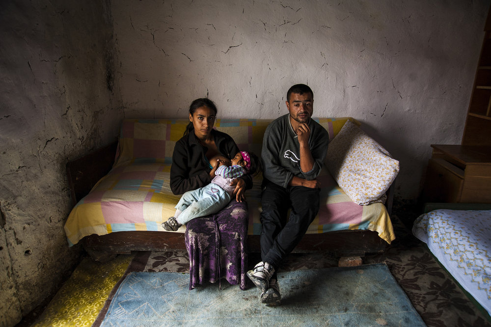 Radu and Cosmina Hendre sit on their bed in their one-room clay home without electricty, running water, or even a door in Cheriu, Romania on May 14, 2013. With debts of nearly $1,000 (US) owed to Romani money lenders, Radu is unable to travel to the nearby city of Oradea to find work, as the lenders have vowed to kill him if he is caught.