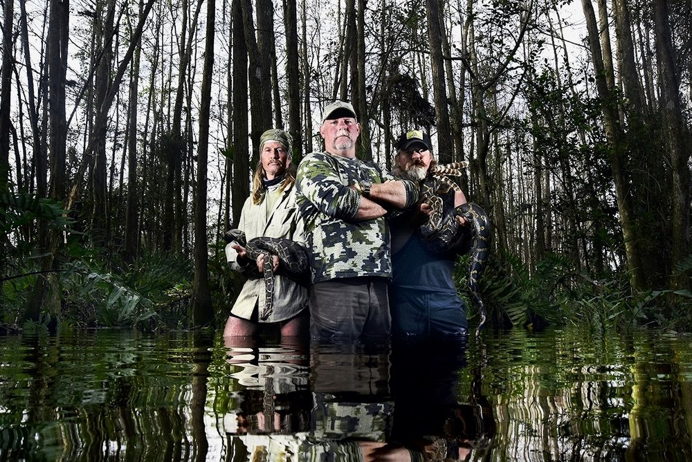Bill Booth, (C), Duane Clark, (L), and Dusty Crum, (R), pose for a portrait after catching a pair of pythons deep in the Everglades Wildlife Management Area on February 10, 2016. The Cypress Boys, as they are known, have caught thirty-two pythons to date, putting them well in the lead with a few days left in the Python Challenge.