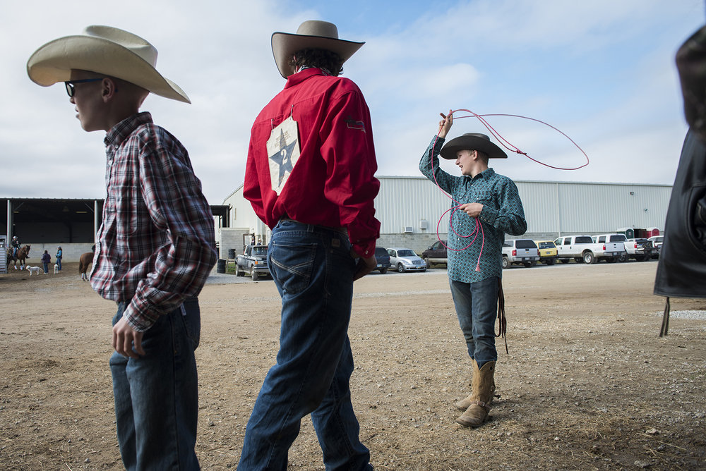 High School rodeo bull rider, Chance Fryer, right, jokes about girls with his friends, Clay Fackler, center, and Gus Joseph, left, while practicing roping techniques before his final ride of the season at Henderson's Arena in Jackson, Ohio on November 4, 2017.
