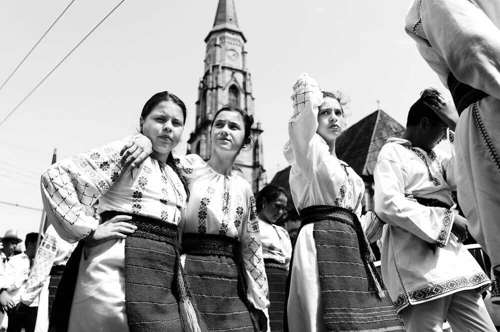 Youth in traditional central Romanian outfits parade through the city square in Brasov, Romania on June 18, 2016.