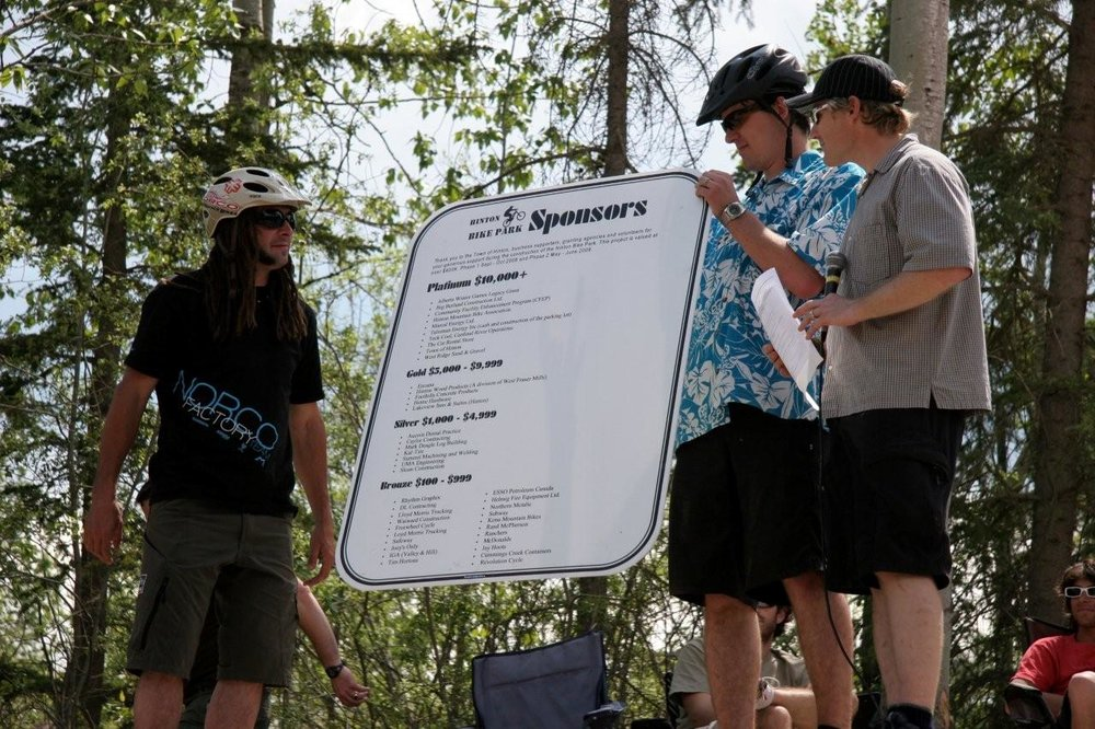 Jay Hoots (left), Jay Hore (middle) and Stephen Hanus (right) displaying the sponsor board for the Hinton Bike Park