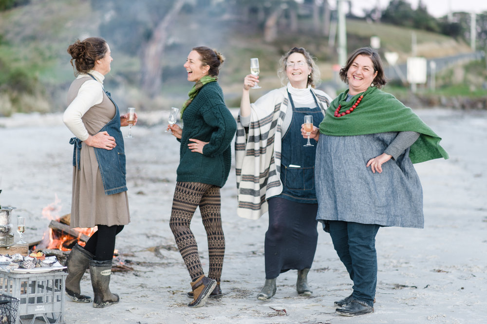 ladies on a beach with beach camp fire and glass of bubbles'Photo Samara Clifford