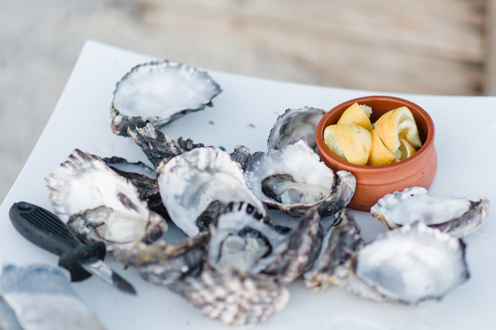 Fresh oyster plate on the Beach with lemon wedges.