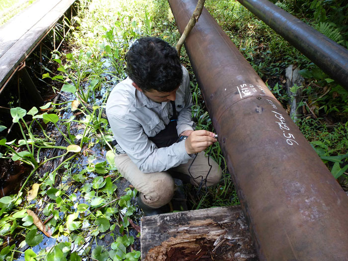 E-Tech hydrogeologist Ricardo Segovia taking ultrasonic measurements of the pipeline