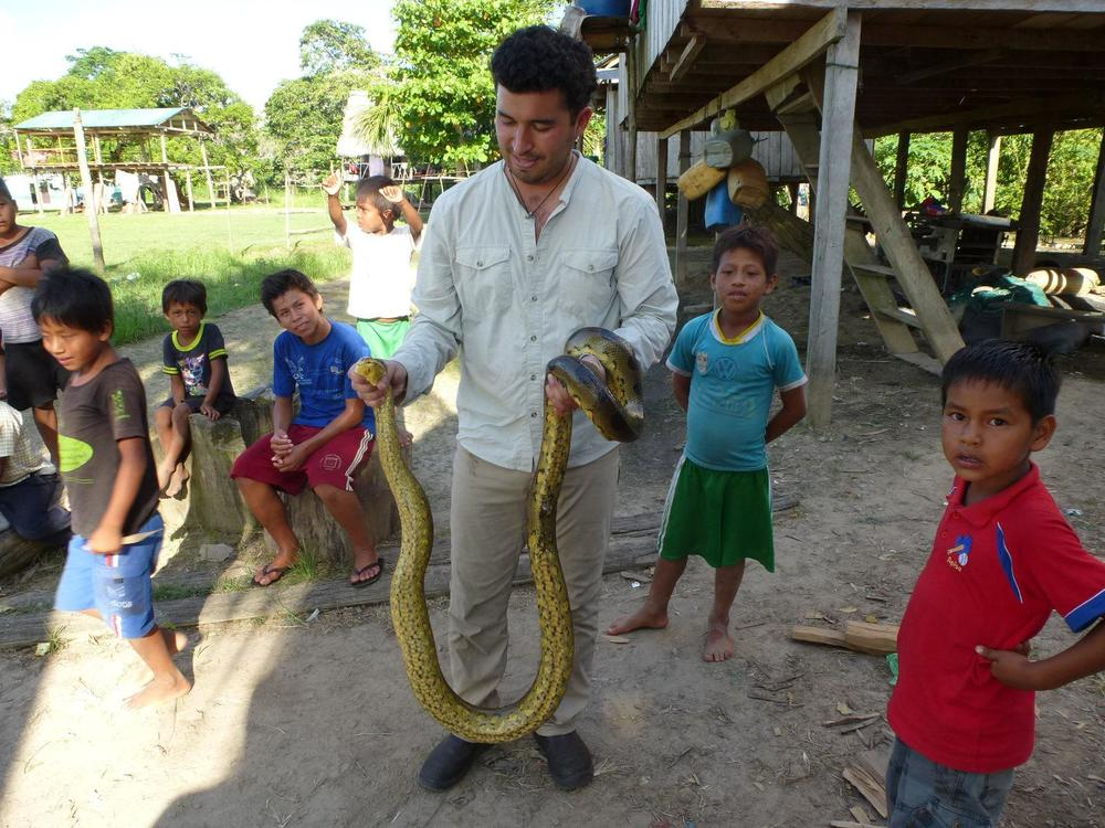 Ricardo Segovia with a boa and local children in Pacaya Samiria