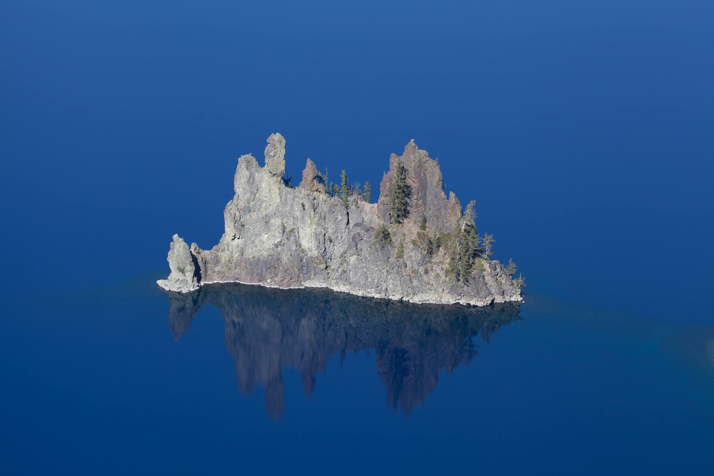 Phantom Ship sailing the glassy waters of Crater Lake.