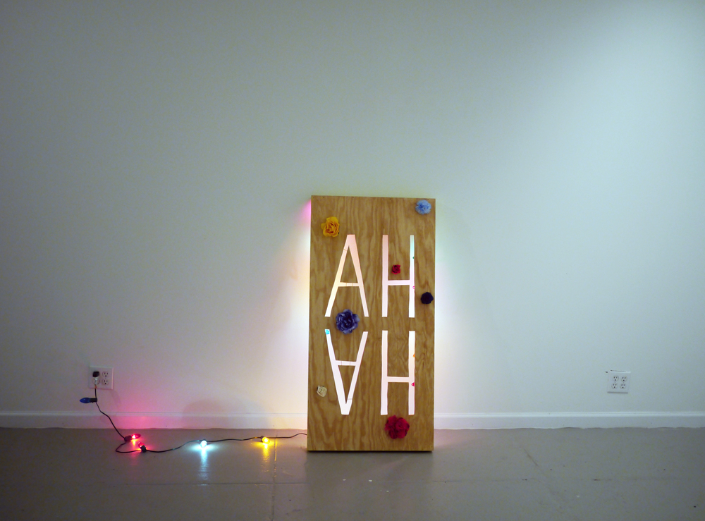 "Lizzie Wright.  AH HA . plywood, paint, colored christmas lights, fake flowers. 48"" x 24"" x 6"". 2013."