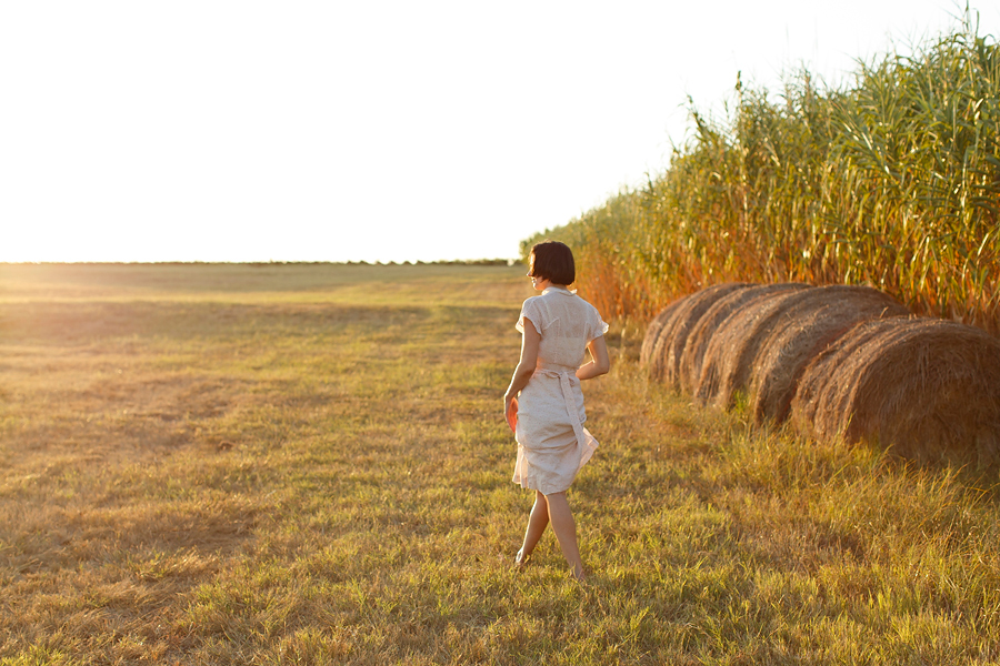 Golden hour in Texas with Dalena VIntage, bales of hay and a vintage 1930s dress. Photo by Nicole Mlakar.