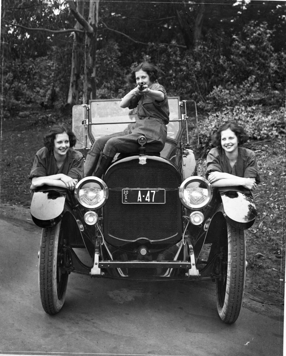 Saucy Snapshots. Three women, a car and a gun, 1920s.