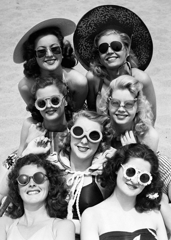 Vintage beach style. A group of women at the beach wearing sunglasses, 1940s.