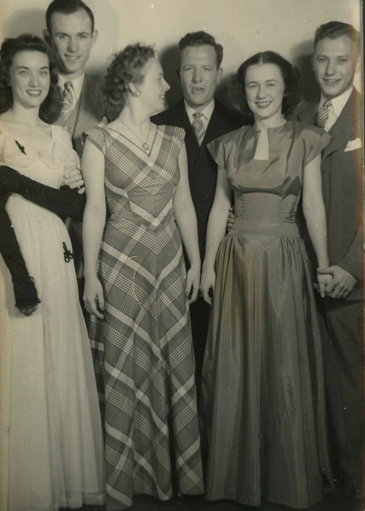 A couples photo equals more dresses to admire! Long gowns in solid and plaid satin were all the rage in the 1940's. These gals are on top of it!  Found here.
