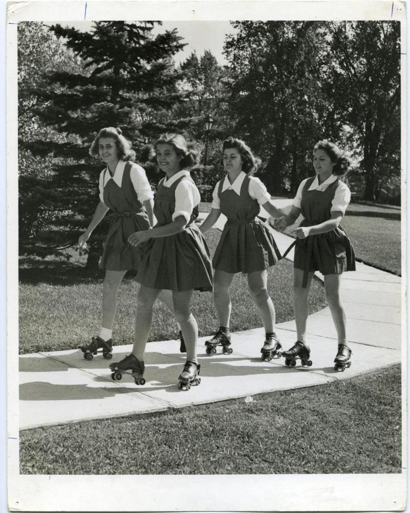 Vintage photo of girls rollerskating in skirts.