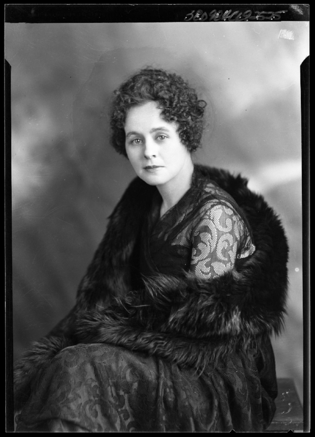 Woman photographed sitting on a bench by Julius Born. She is wearing a dark-colored fur stole over a dark lace dress. Her hair is short and curled in typical 1920s style.