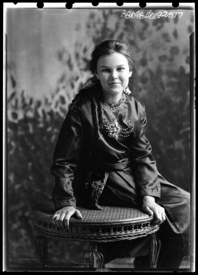 Portrait of a young woman sitting on a table taken by Julius Born. She is wearing a dark-colored dress with embroidered flowers on it, a ring on each hand, and a necklace. Her hair is long and curled with a striped bow in the back.