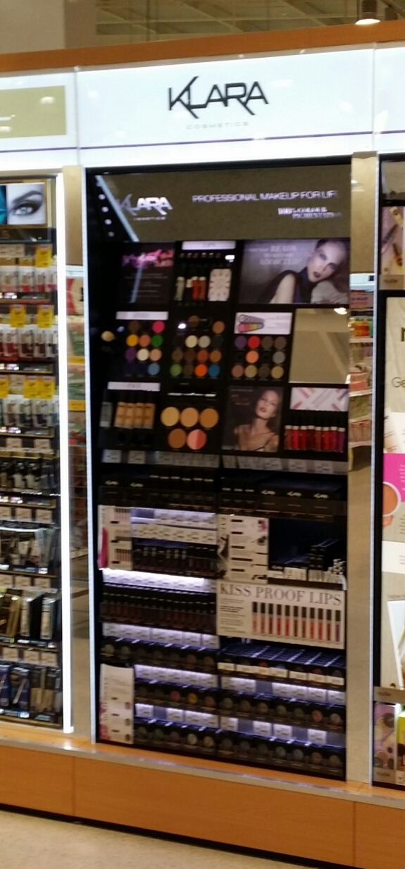Klara Cosmetics Coles infill.  Features etched backlit charcoal mirror, LED lighting, Tester panels with security retraction devices. Push feed stock trays from steel and acrylic.