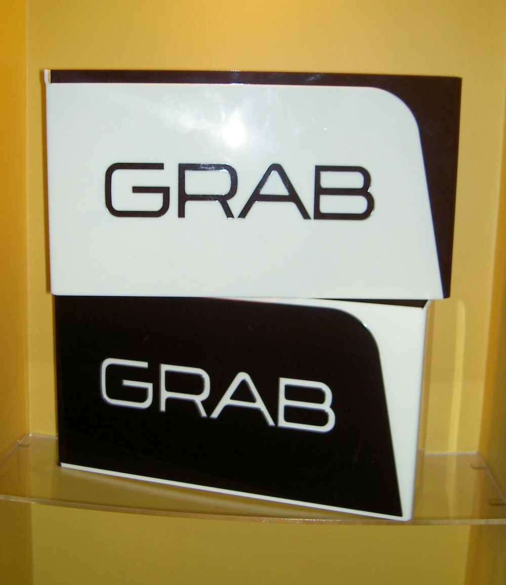 Grab clothing. Signage devices from black and cream acrylic