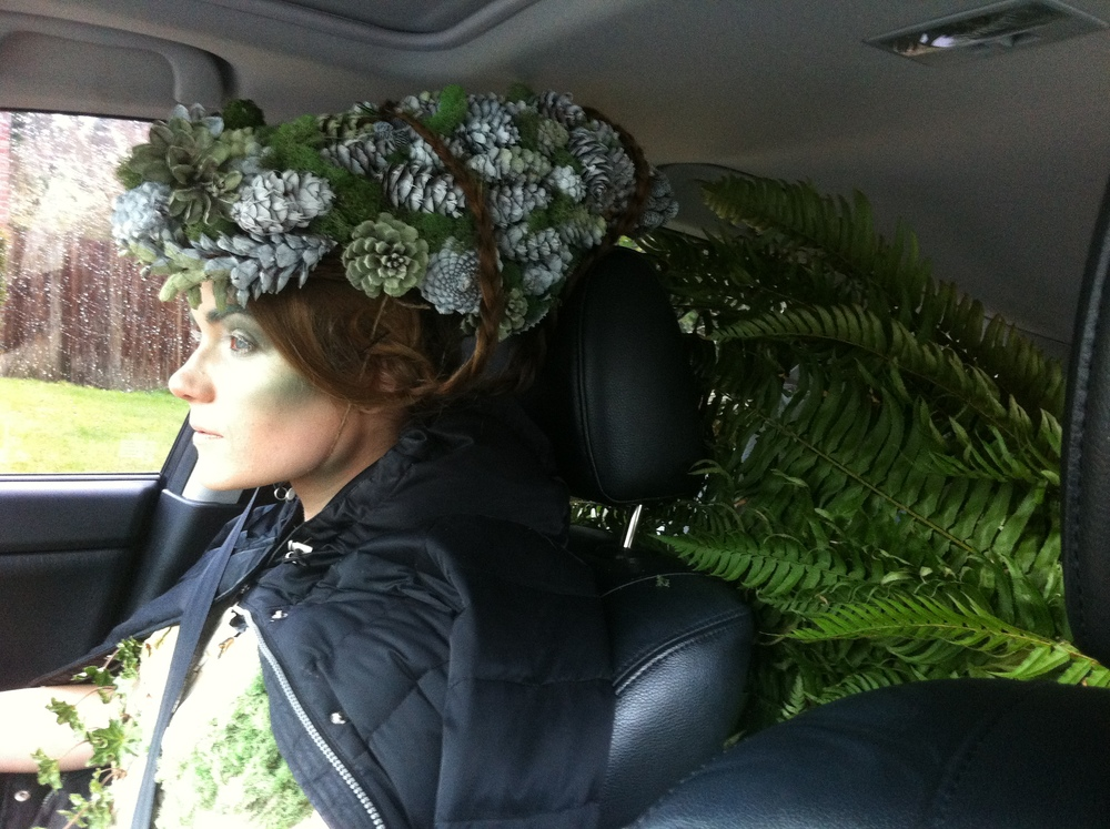 Meredith wearing the completed headdress on our way to the location--due to its weight, she was resting by balancing it on the headrest. The ferns creeping into the front of the car are the massive skirt that we somehow managed to fit in my backseat.