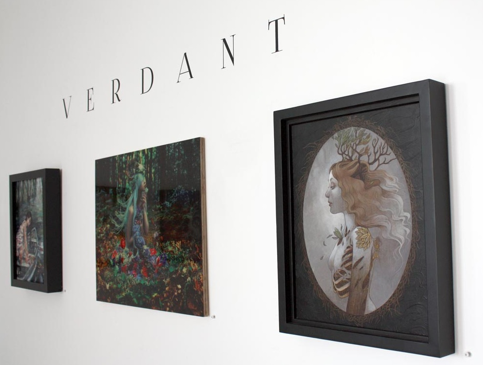 "Display at Modern Eden's ""Verdant"" group show, photo courtesy of Modern Eden. Resin-glazed wood print pictured in middle of Kindra Nikole's ""Of Withering Abundance."""
