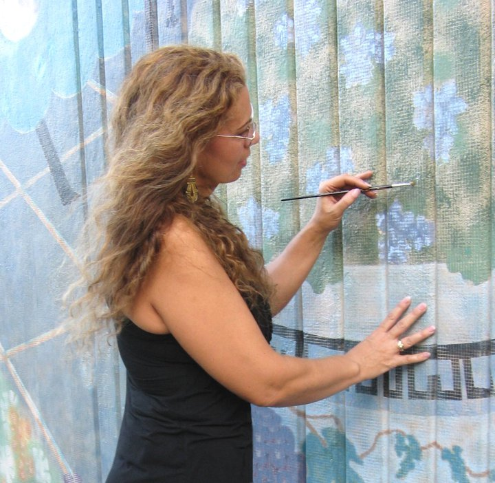 In-action shot of Ana Livingston, Fine Artist and Muralist. Restoring the famous Avenue du Jardin Mural