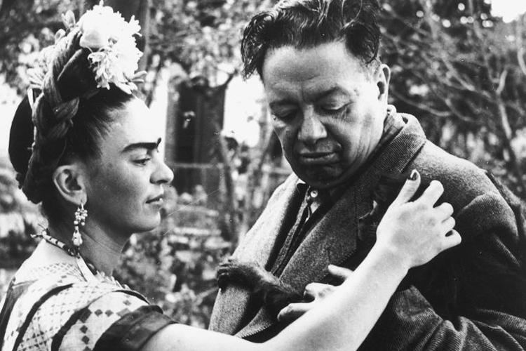 Frida Kahlo and Diego Rivera with one of their pet monkeys.