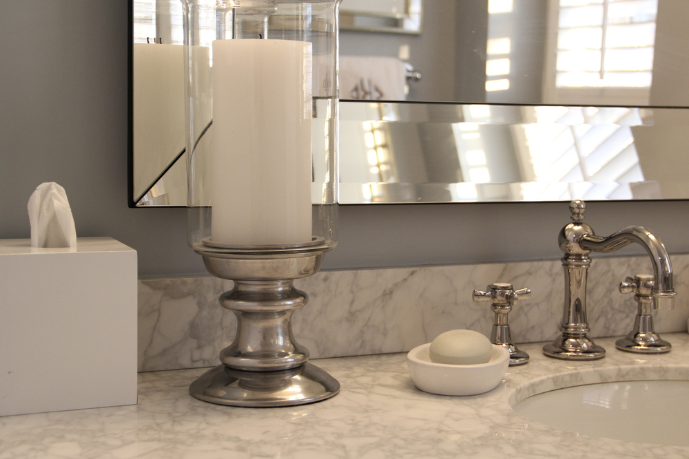 The left side of my bathroom countertop includes the West Elm White Lacquer Tissue Box Cover, a Pottery Barn Hurricane with a White Pottery Barn Pillar Candle, and the Crate & Barrel Pure Oval Soap Dish paired with a fragrant bar soap from Anthropologie.