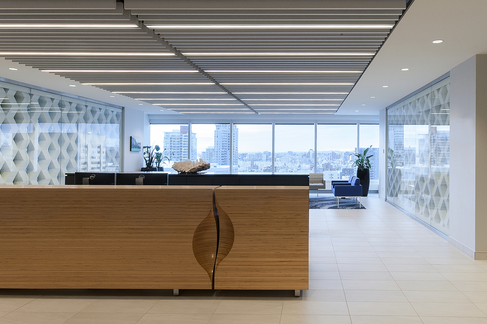 Clean lines and crisp finishes define the final design for this corporate office renovation project. An exposed-edge plywood reception desk anchors the space with custom rugs, Herman Miller furniture, and Modularts dividers complimenting it.