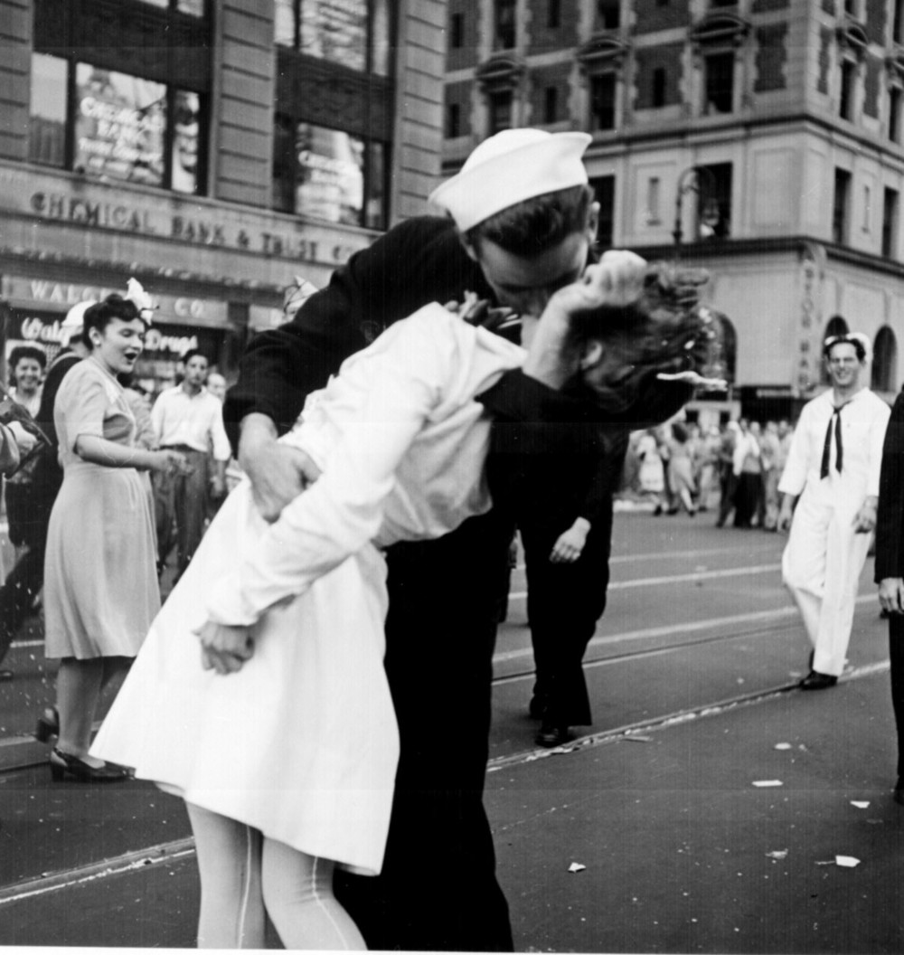 Kissing the War Goodbye by Lt. Victor Jorgensen Lt. Victor Jorgensen / U.S. Navy photograph, The famous kiss from a different angle. with nurse Gloria Bullard in the background. Bullard's account of the afternoon helped Don Olson determine the exact time of the kiss. via Wikimedia Commons