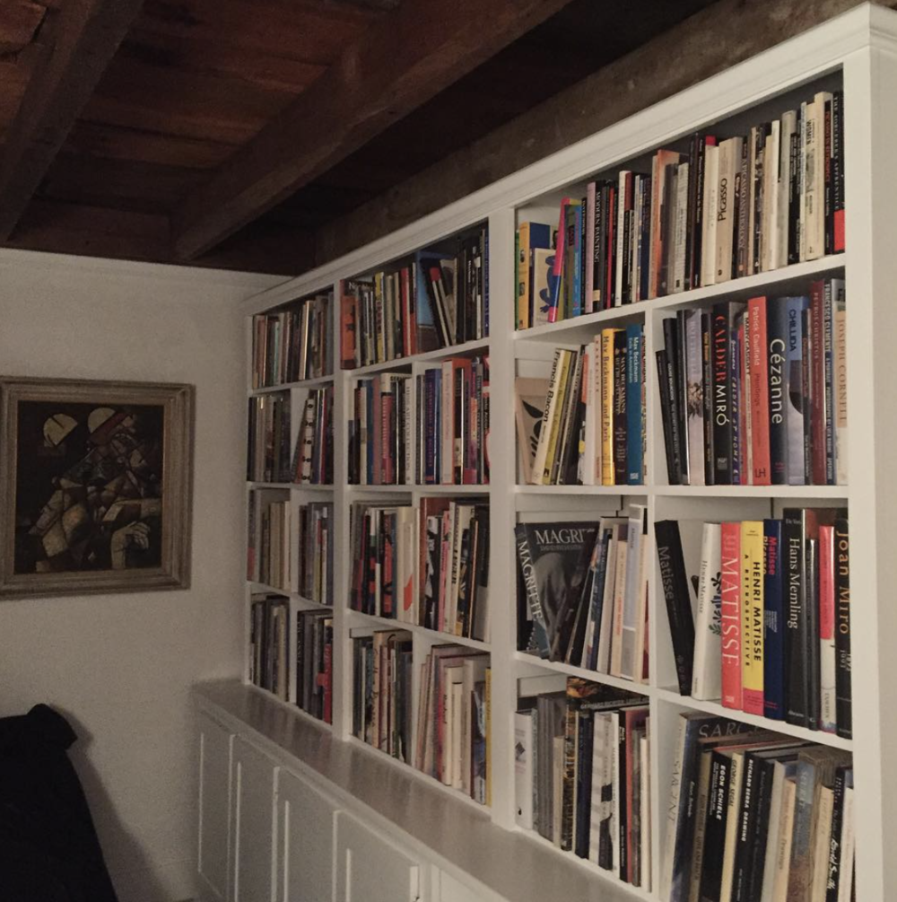 A wall of artist monographs in Marc Leavitt's collection.