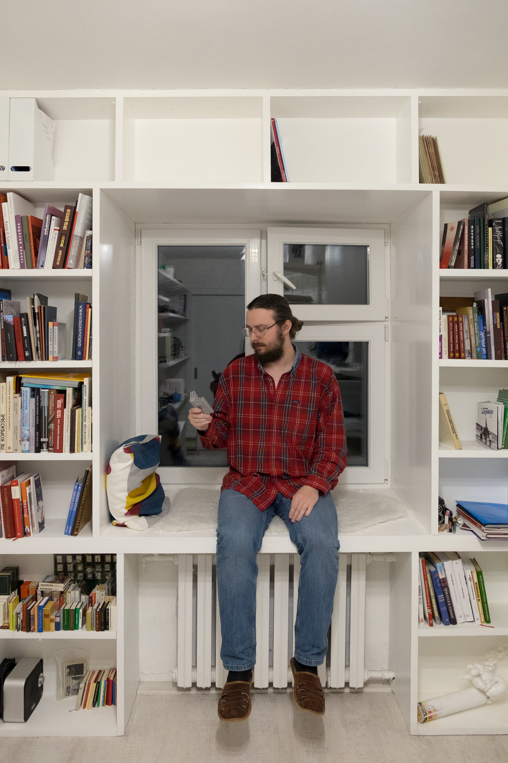 Photographer  Mikhail Emelchenkov  in his home office viewing a miniature photobook