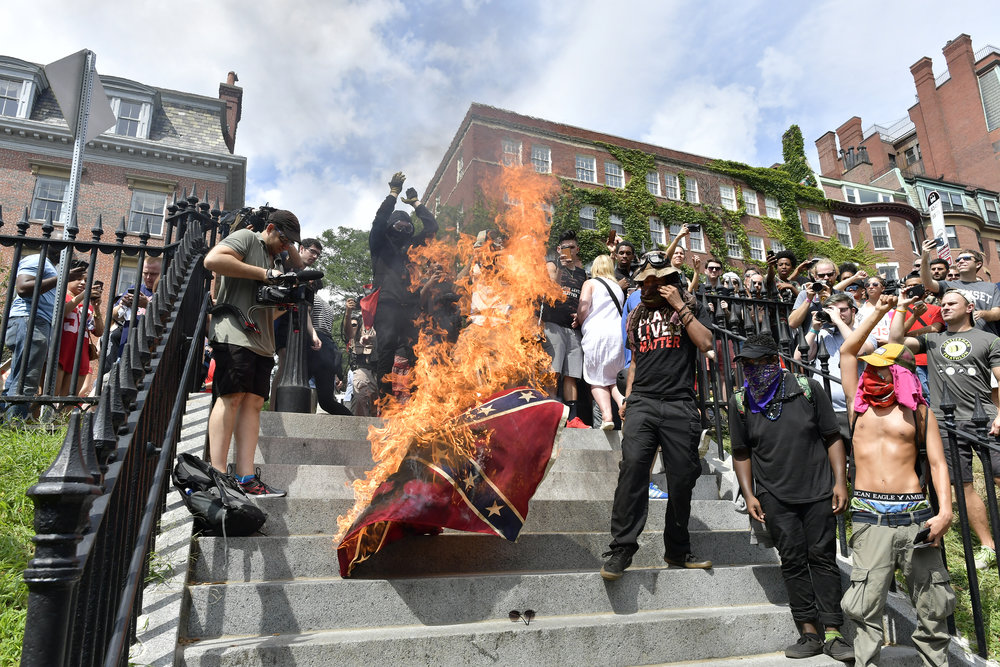 BOSTON, MA Saturday, August 19, 2017 -- Black Lives Matter protesters burn a Confederate flag as tens of thousands of demonstrators turned out to protest the Boston Free Speech Rally on Boston Common.