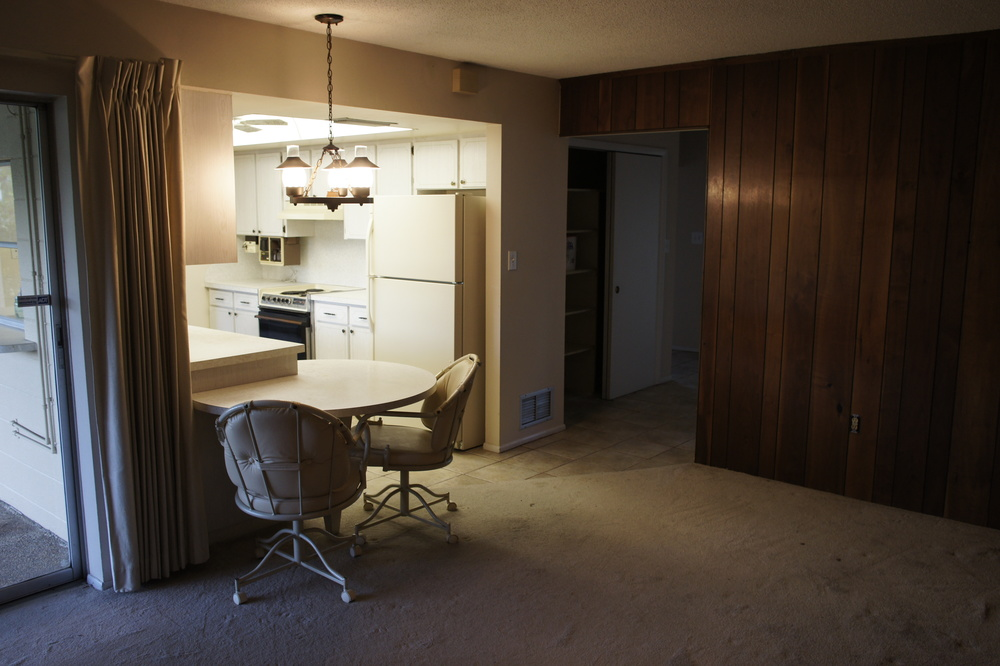 Dark wood paneling and the galley kitchen
