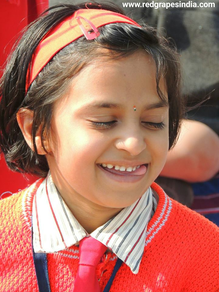 Cute smile of kid on 26th Jan Republic day celebration at Wine information center by Red Grapes at Wine park, Vinchur, Nashik, Maharashtra, India