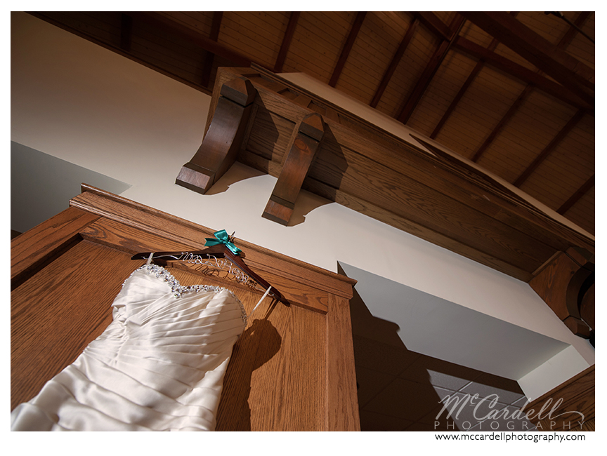 Ivory bridal gown from Diva's Boutique and Bridal hangs off wooden personalized hanger in Greensboro, North Carolina. Images courtesy of McCardell Photography, a Greensboro, North Carolina Wedding Photographer.