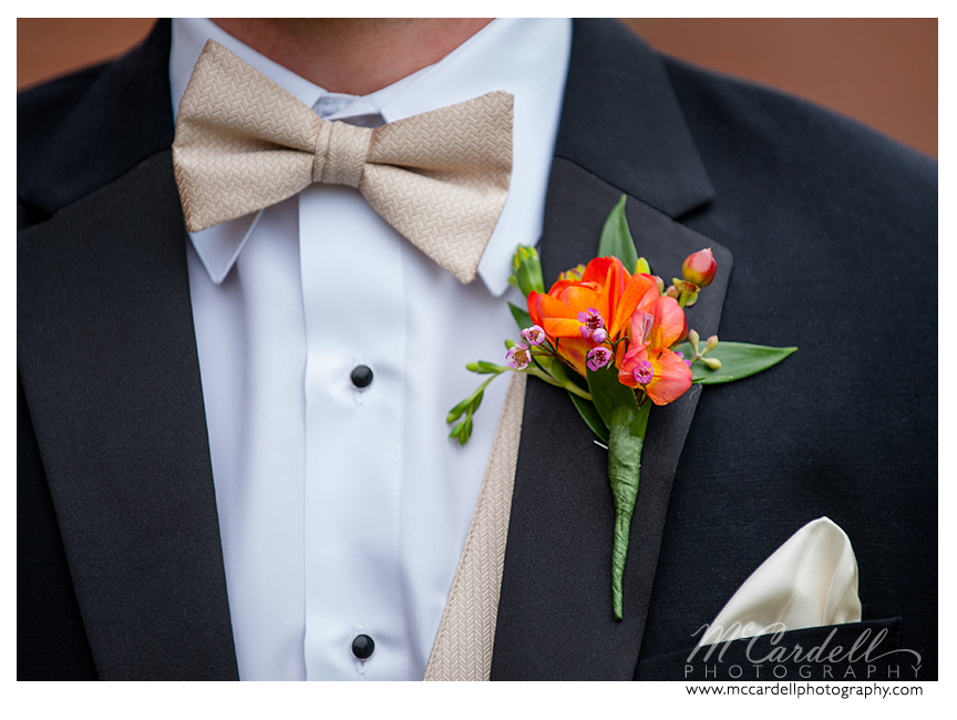 Black suite, ivory bow ties and vest complimented by orange boutonnieres by Botanica Flowers and Gifts at this Starmount Country Club wedding in Greensboro, North Carolina. Images courtesy of McCardell Photography, a Greensboro, North Carolina Wedding Photographer.