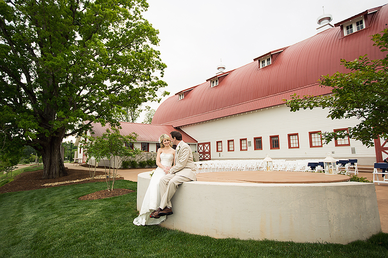 Bride and groom pose together outside the Winmock at Kinderton in Bermuda Run, a TriadWeddings venue. Image by Elly's Photography.