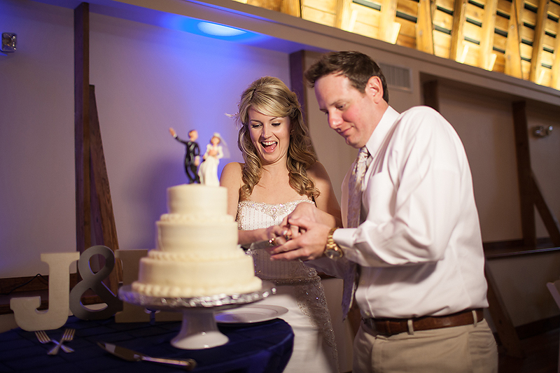 Bride and groom cut their Cheesecake by Alex wedding cake at their Winmock at Kinderton wedding in Bermuda Run, A TriadWeddings vendor. Image by Elly's Photography.